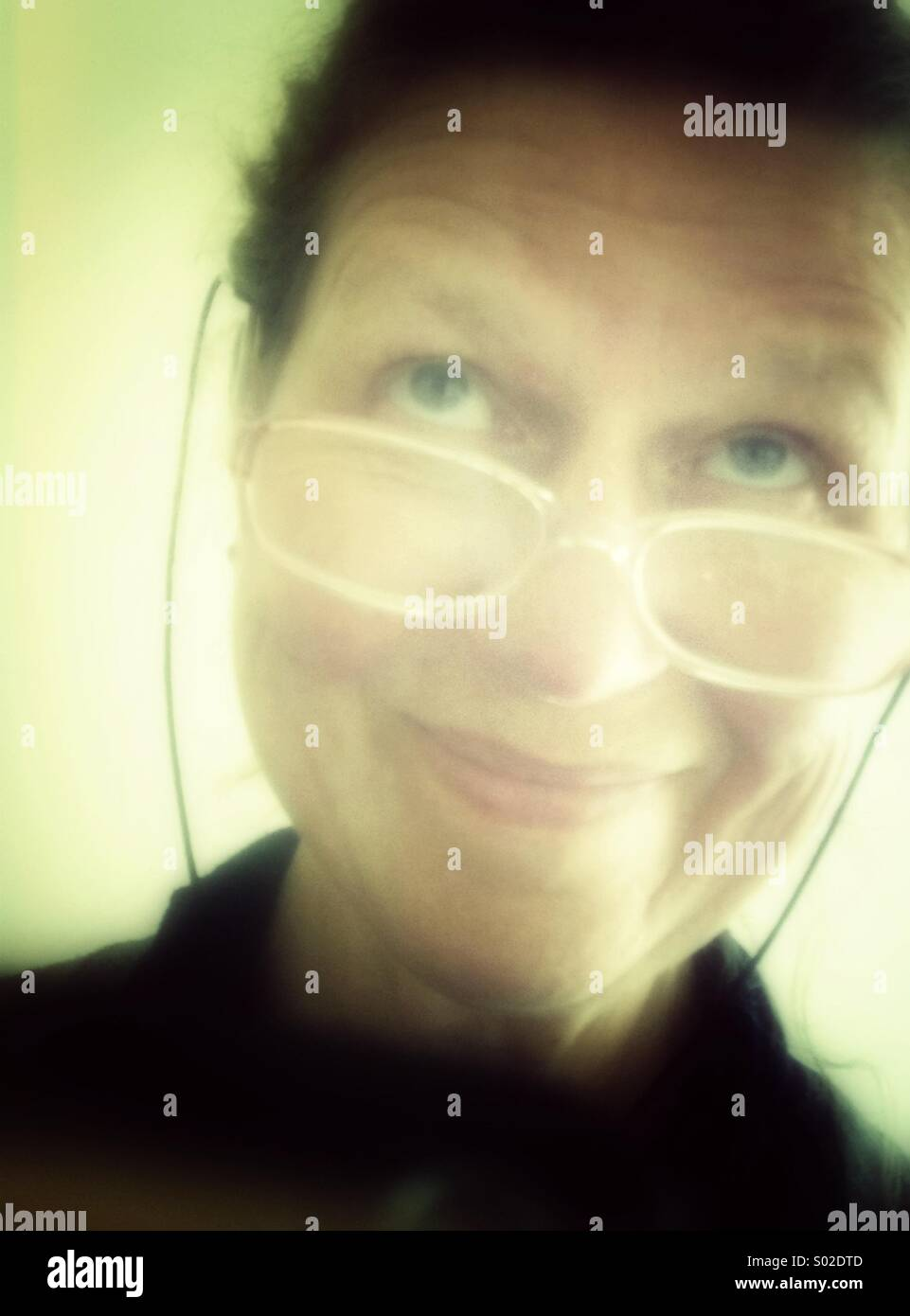 Smiling mature woman wearing spectacles, looking up - Stock Image
