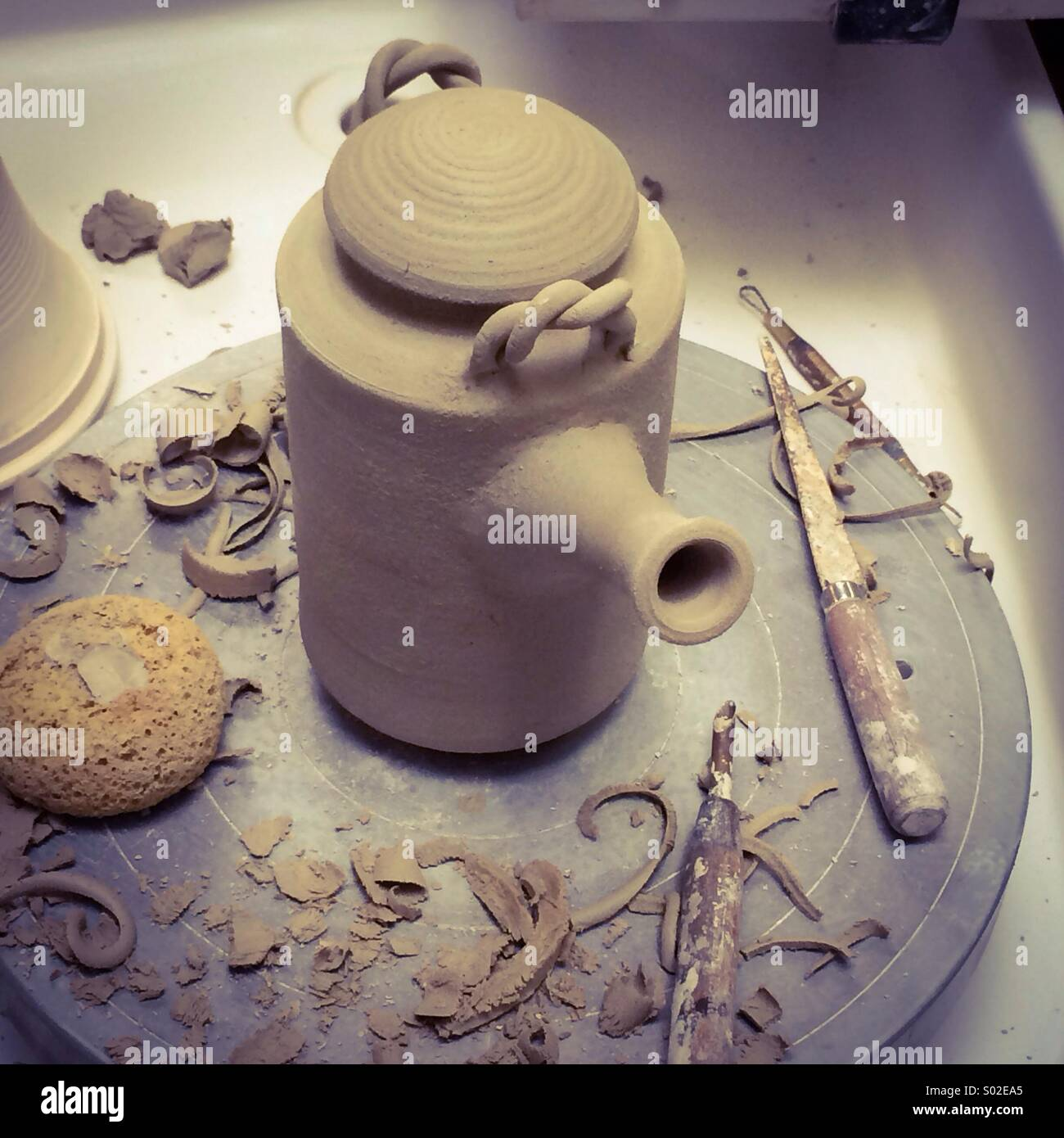 Potter making teapot out of clay on the wheel - Stock Image