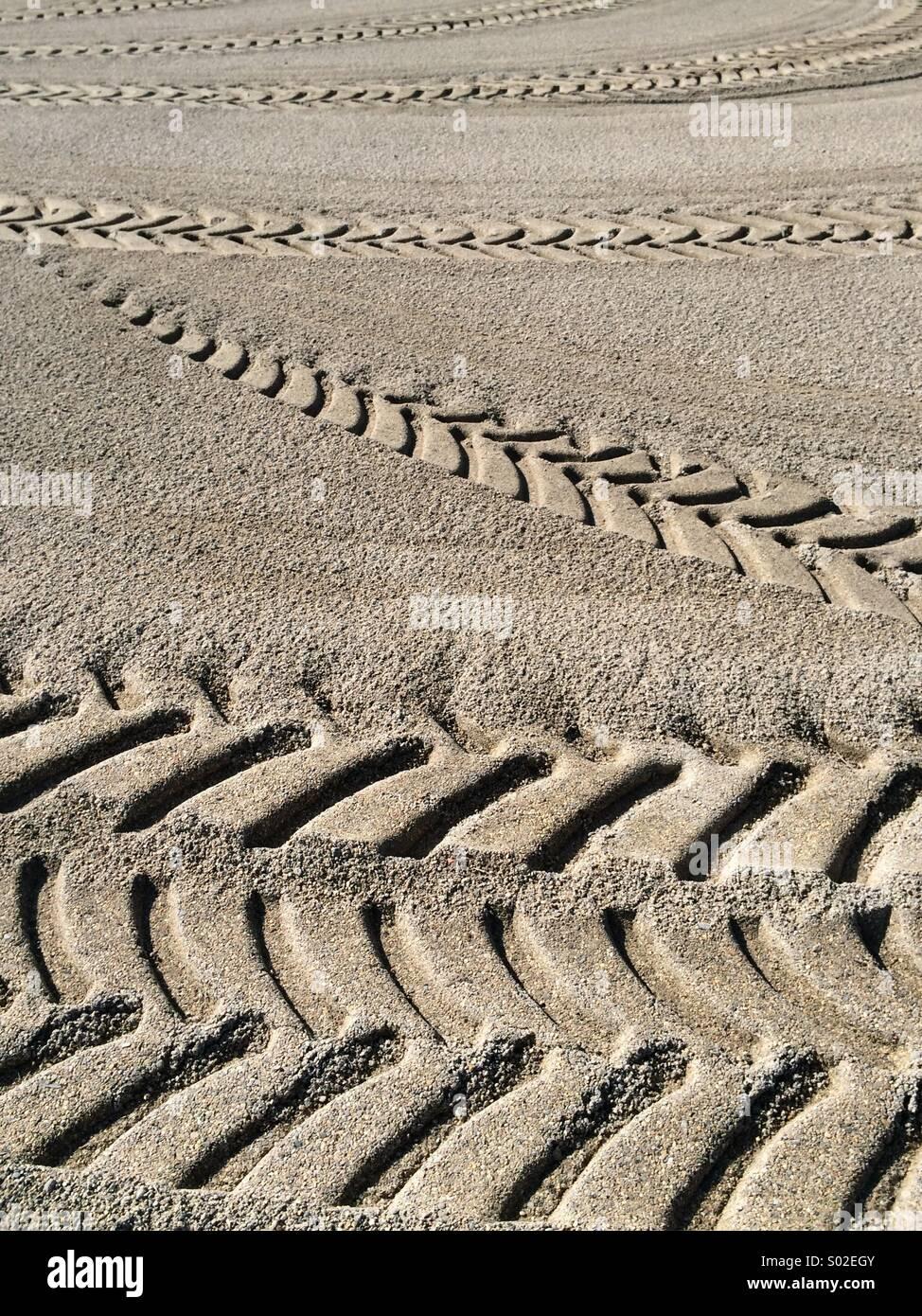 Sand beach tracks print impress trace seashore wheels tyres - Stock Image