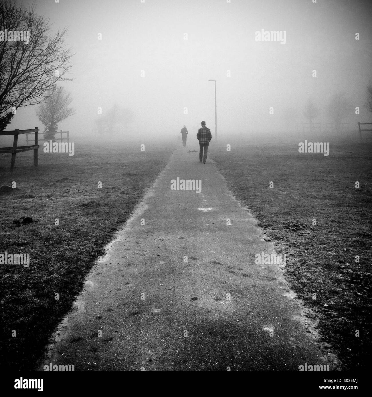 Two figures walk away from camera one ahead of the other along an isolated path through the fog - Stock Image