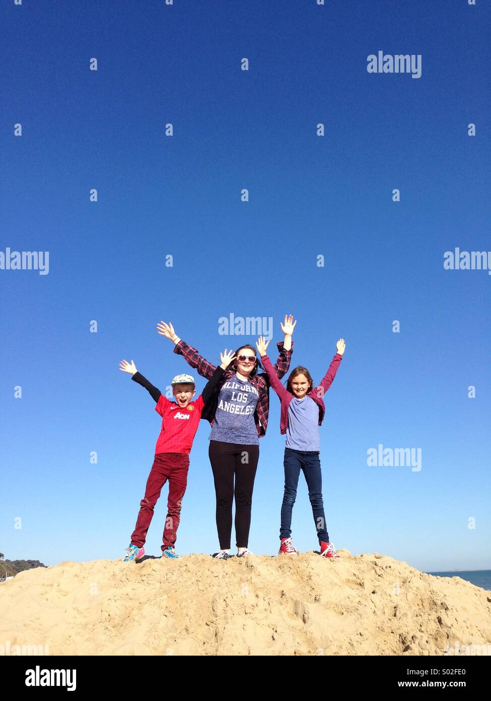 three kids on a sand dune with clear blue sky - Stock Image