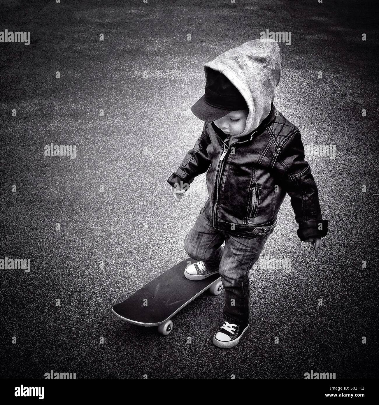 Toddler with leather jacket trying out a skateboard - Stock Image