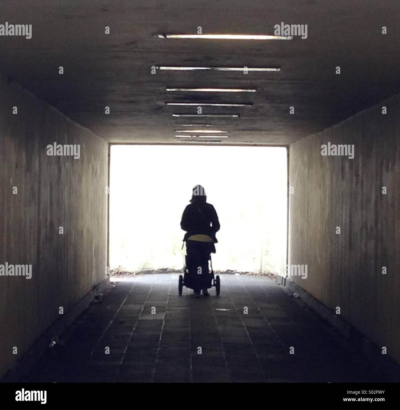 A woman makes her way through an underground subway pushing a pram - Stock Image