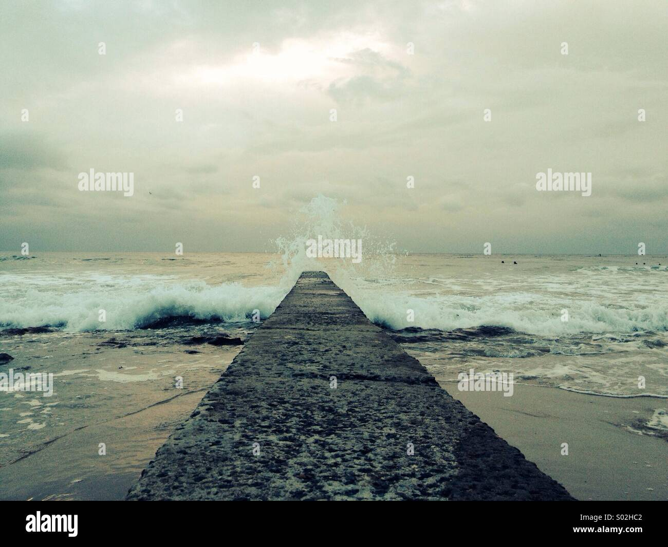 Ocean waves crashing on the jetty under a cloudy sky - Stock Image