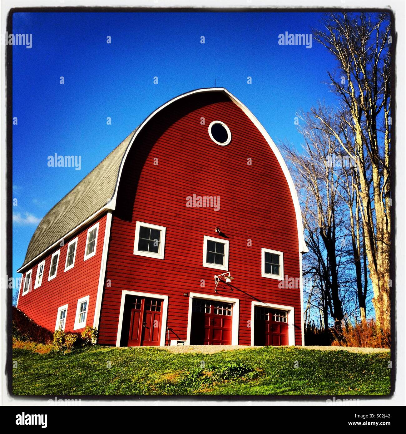 Classic lines on this big, red barn epitomize country living. - Stock Image