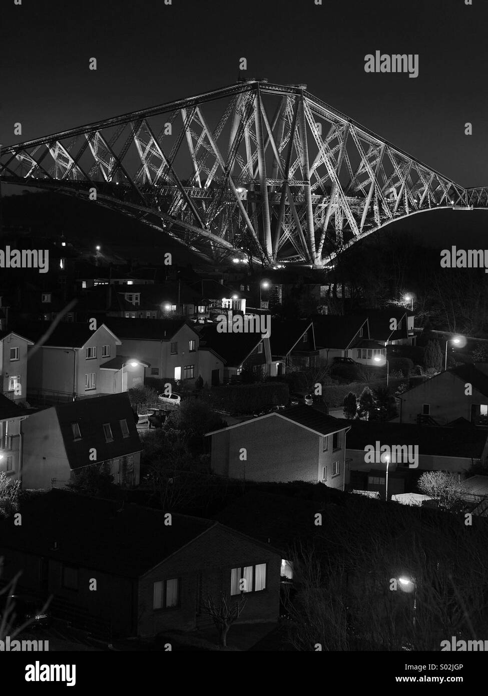 The Forth Rail Bridge viewed across the rooftops of North Queensferry. - Stock Image