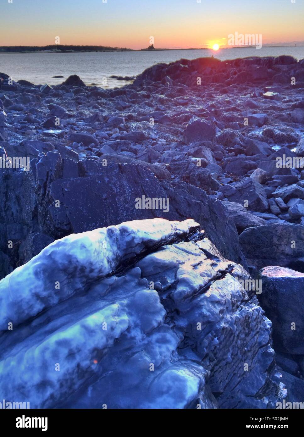 Icy boulder at dawn on the New Hampshire seacoast. Great Island Common, New Castle. - Stock Image