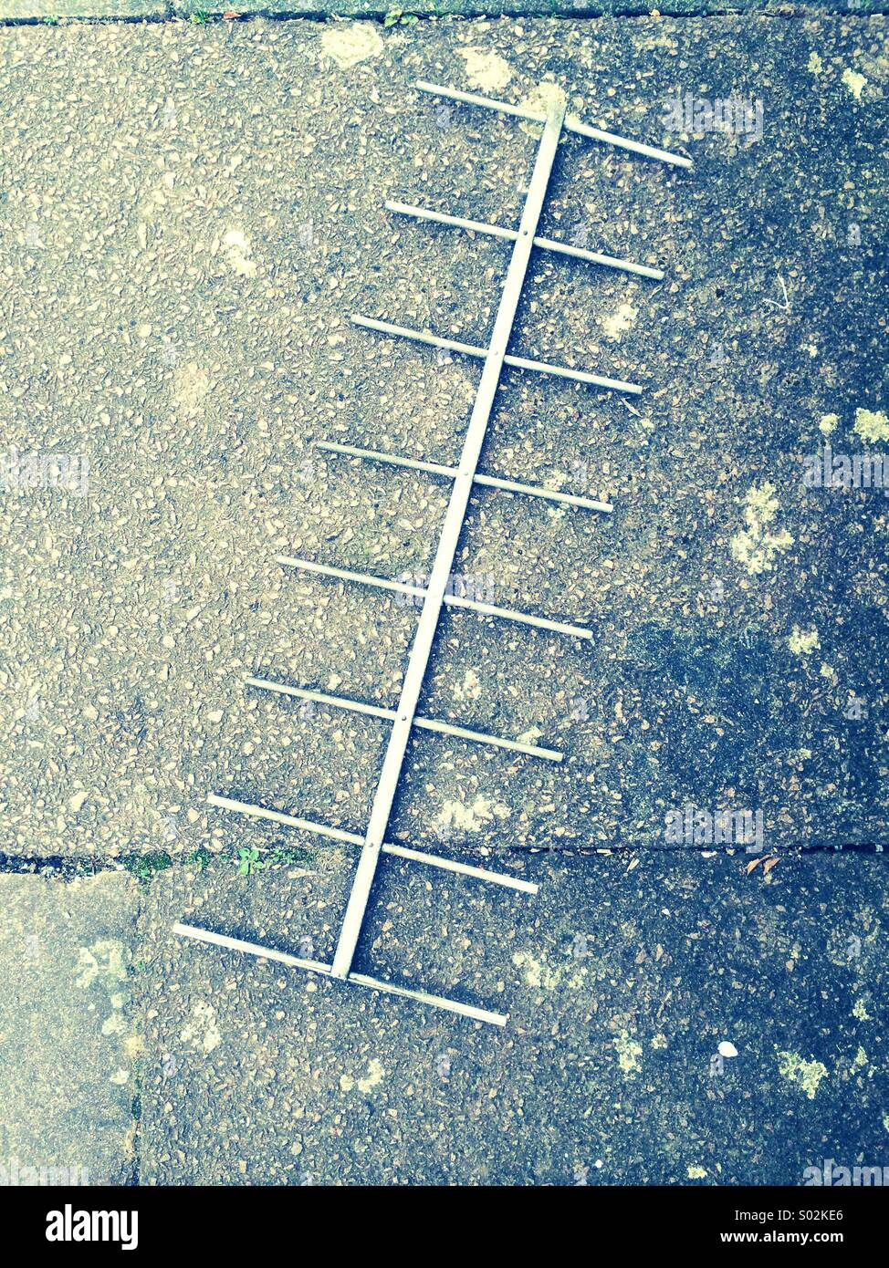 TV arial laying on a pavement, abstract - Stock Image