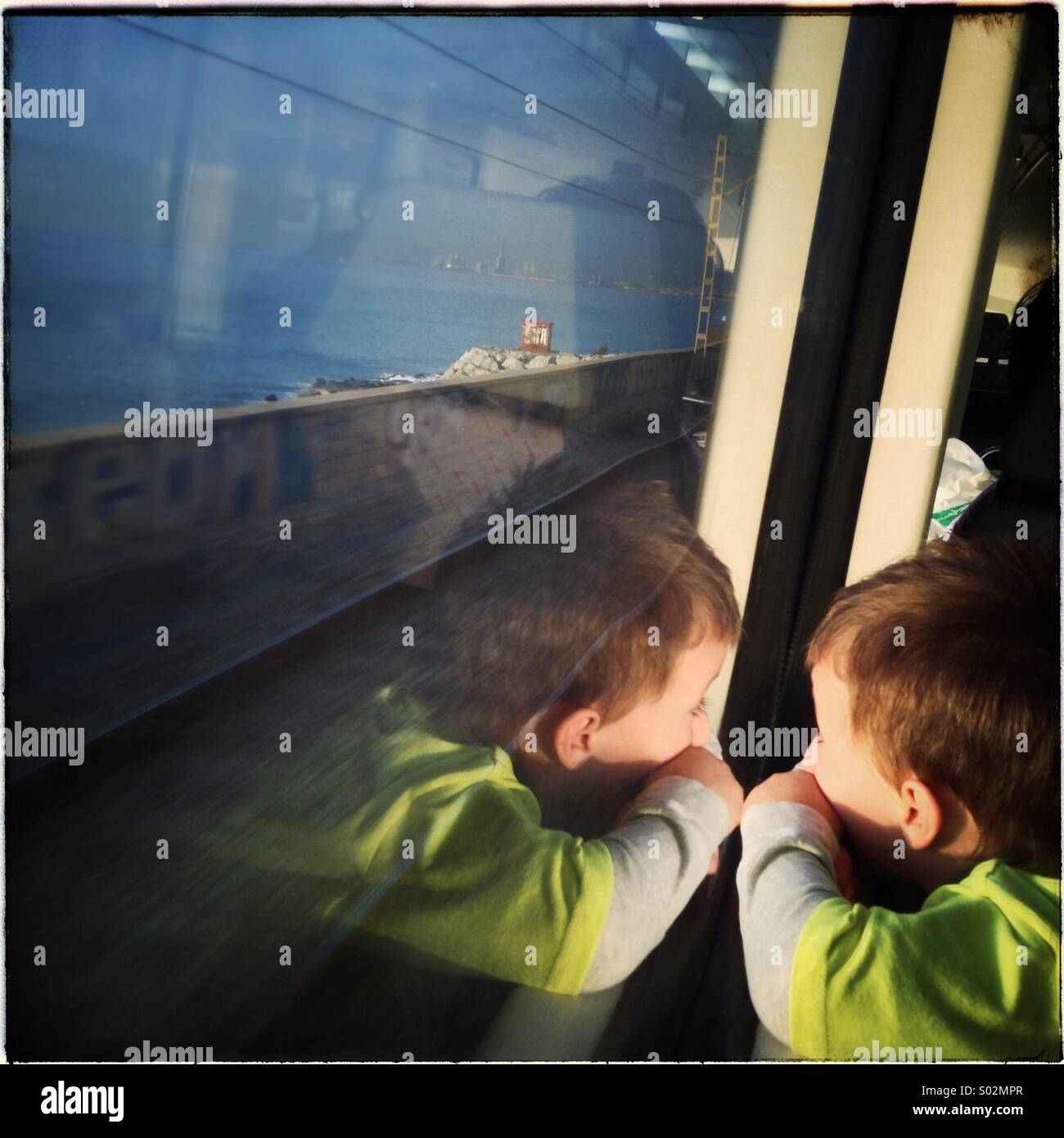 Little boy looking out while travelling on a train - Stock Image
