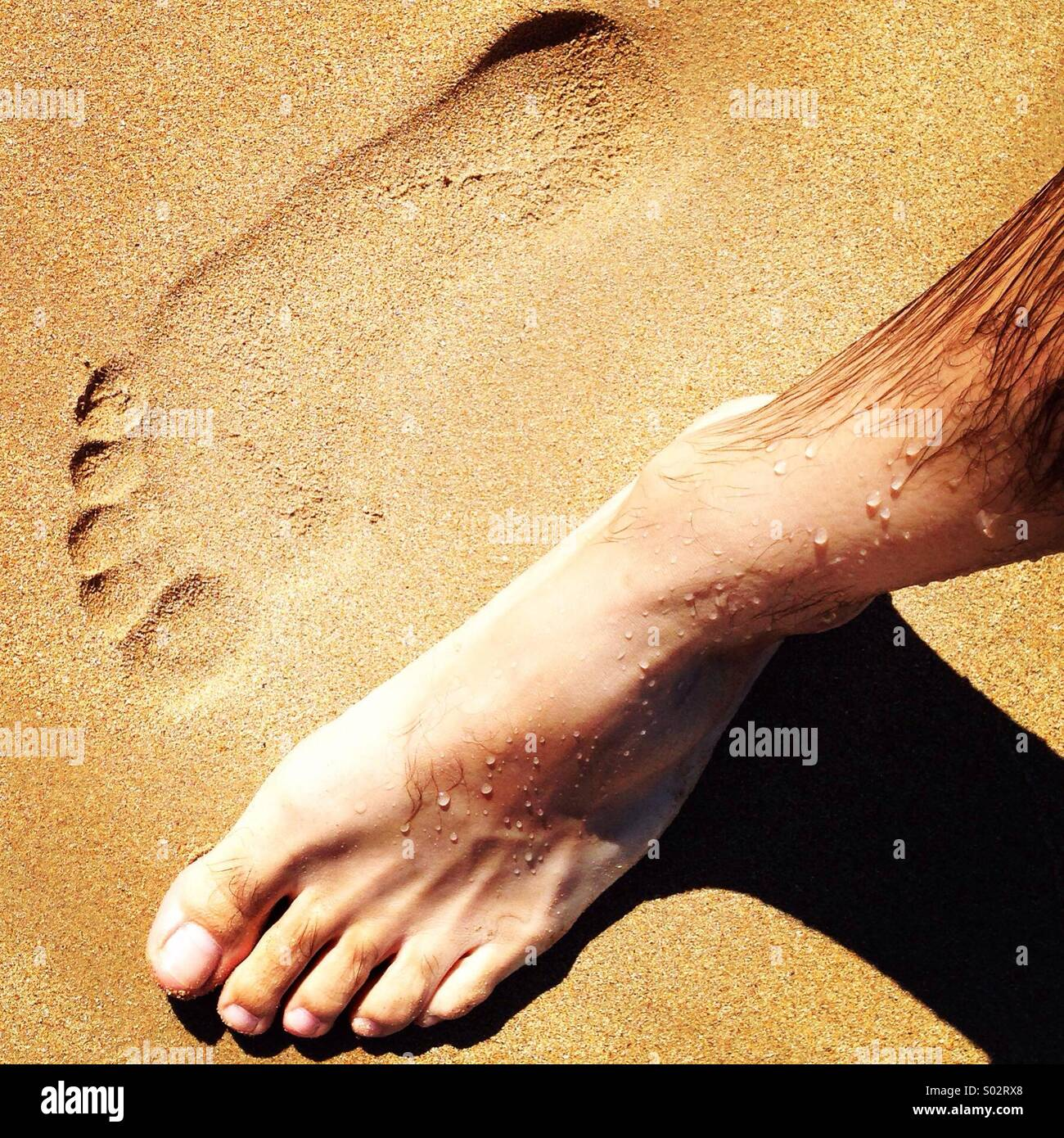 Left foot and footprint on sand - Stock Image