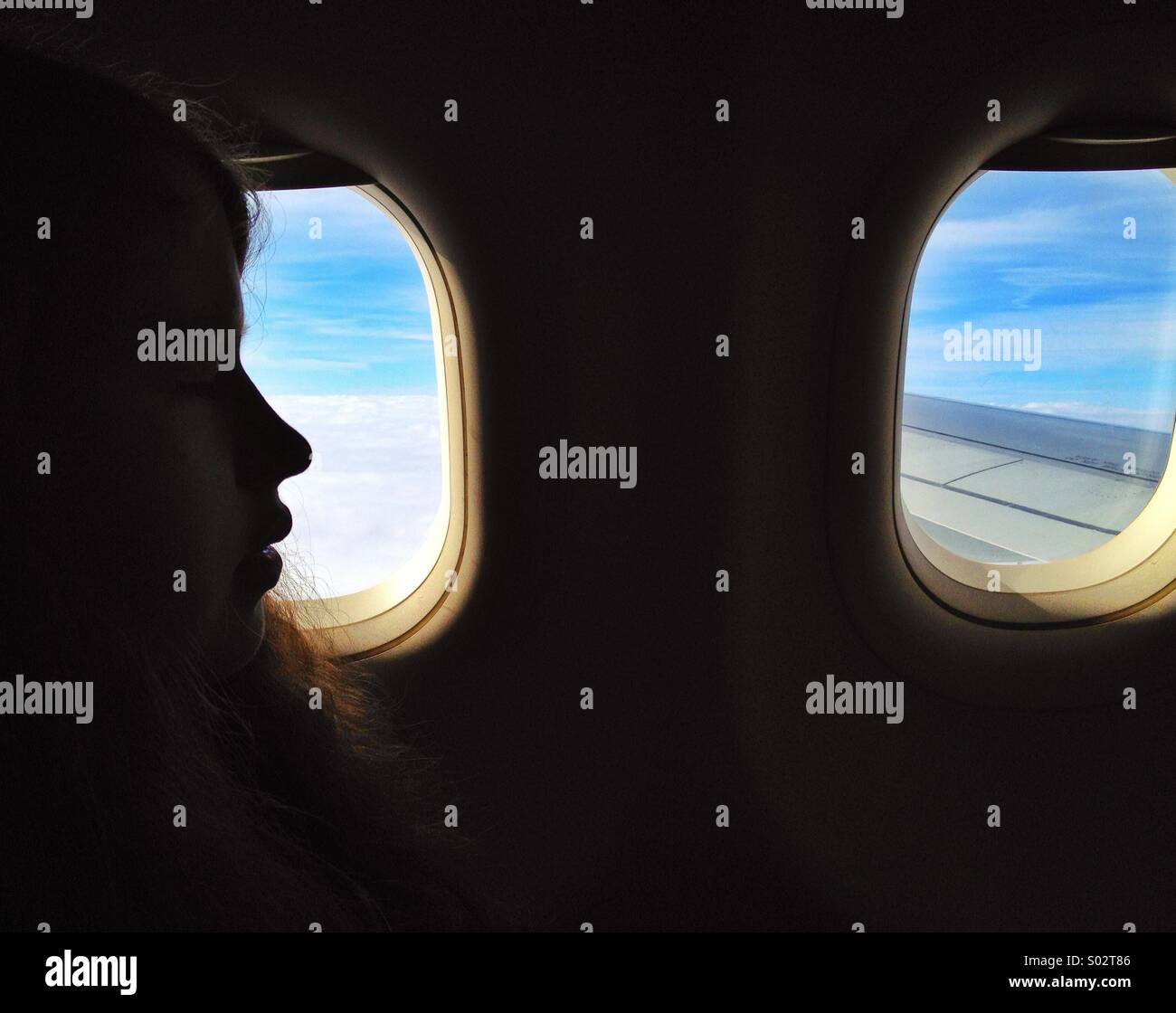 Air travel, teenage girl in profile by window of airplane in flight - Stock Image
