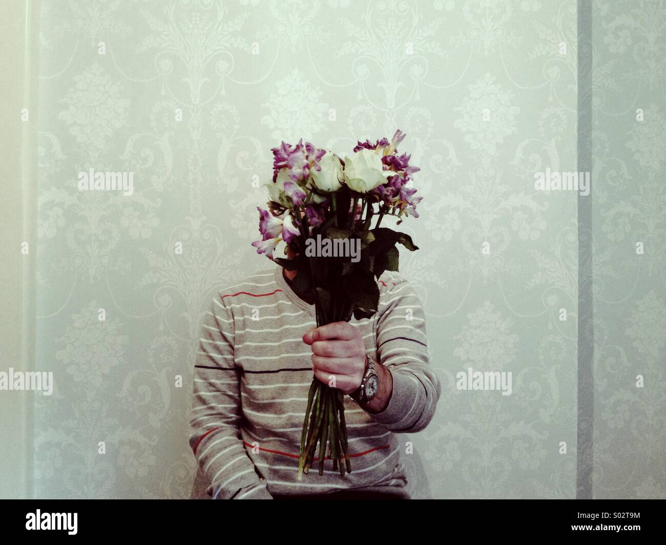 Hidden figure presenting a bunch of flowers indoors against a plain wallpapered background - Stock Image