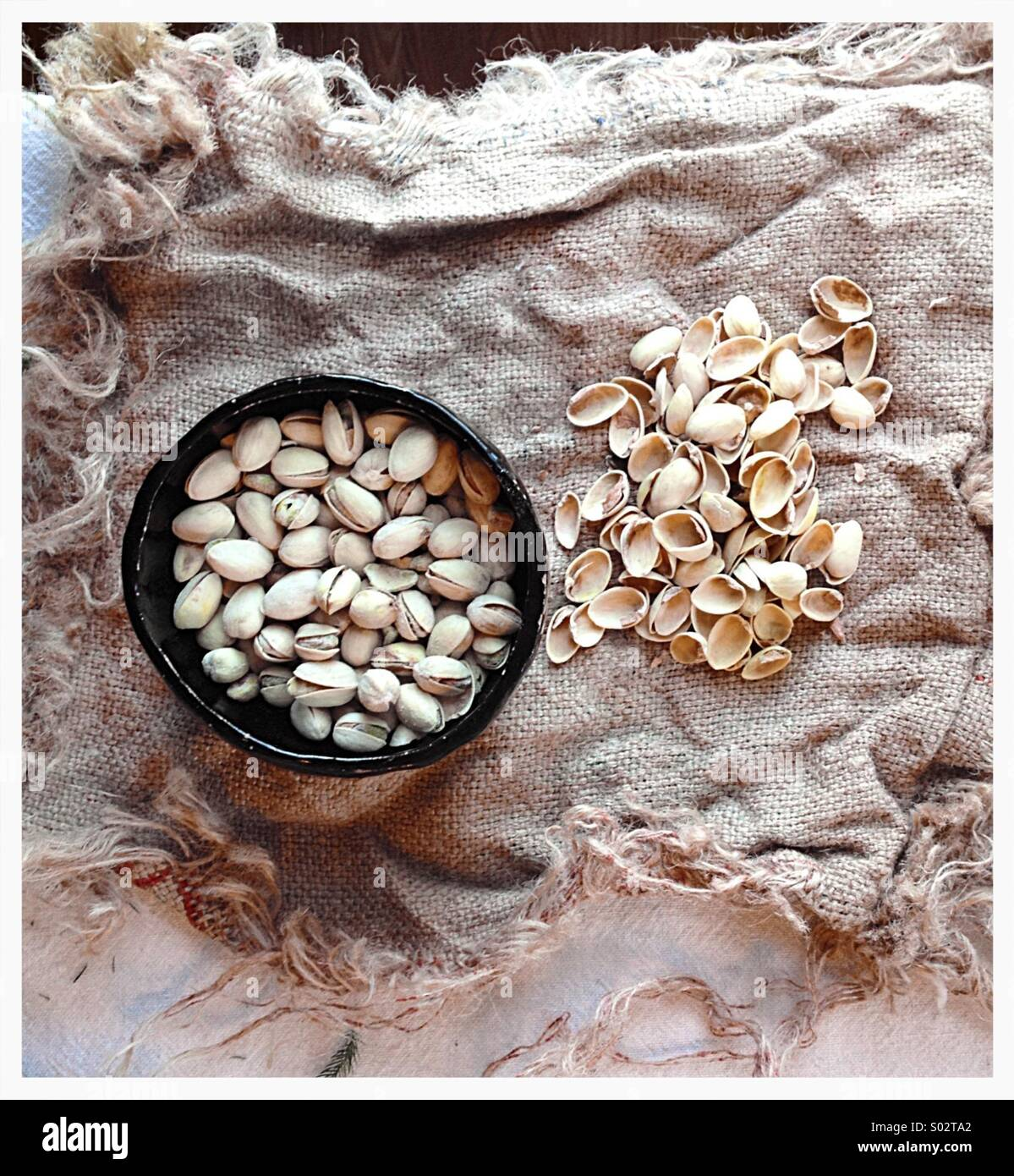 Pistachios in bowl on burlap - Stock Image