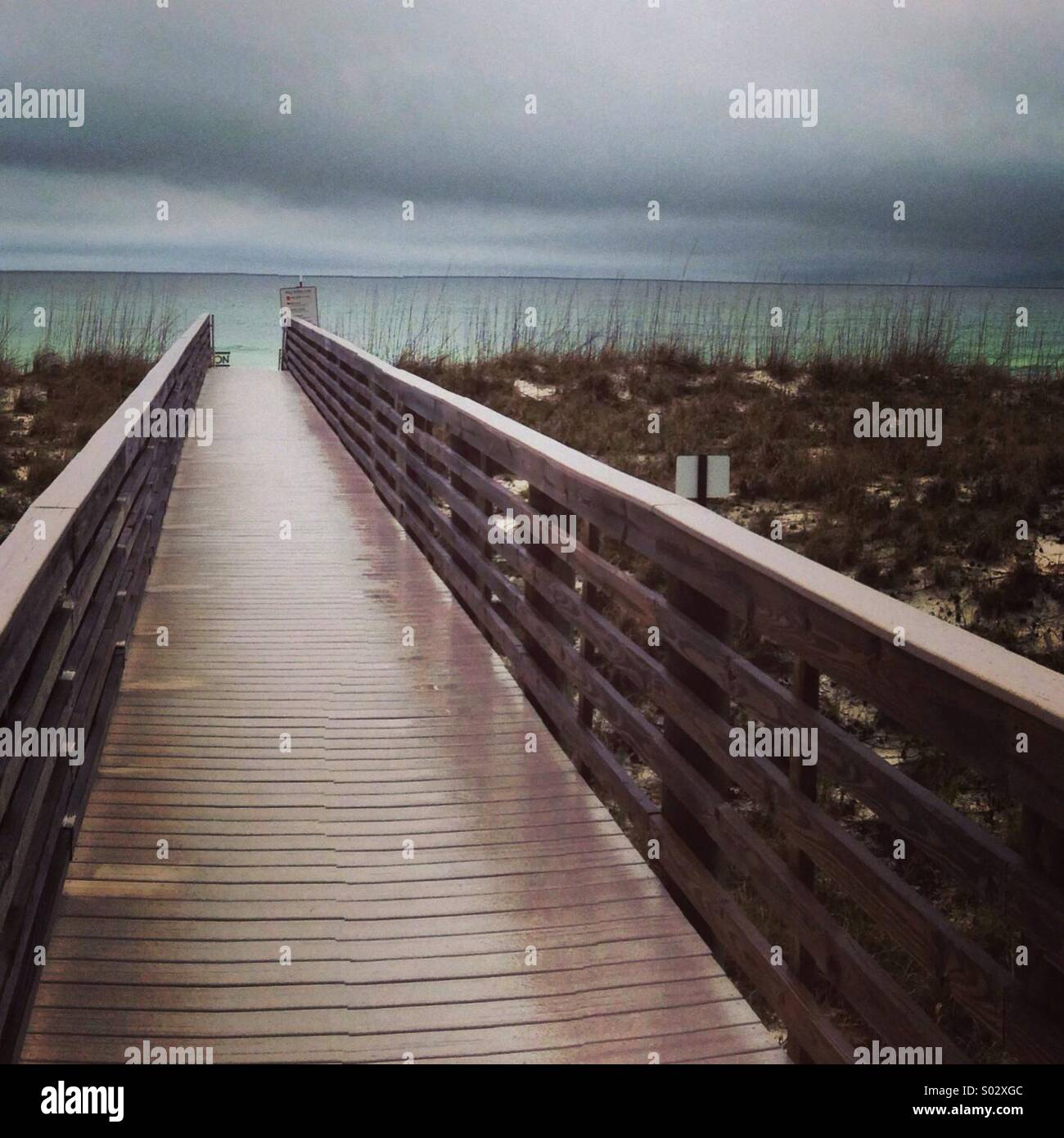 Wet beach walkway and stormy sky. - Stock Image