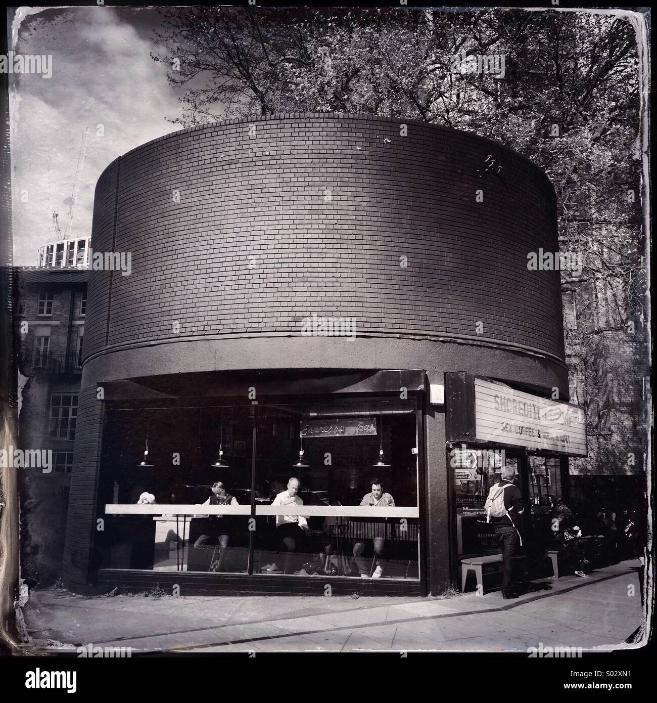 Black and white photo of Shoreditch Grind coffee shop on Old Street Roundabout, London, UK. - Stock Image