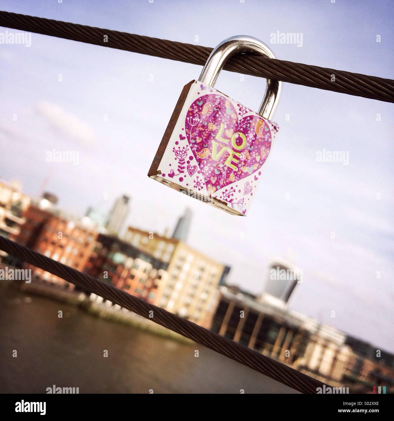 A love lock padlocked to a bridge in London. After the padlock has been locked, the key is thrown away to symbolise - Stock Image