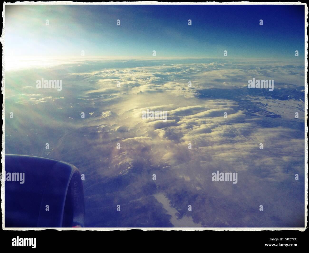 The view of clouds below, from an airplane window. - Stock Image