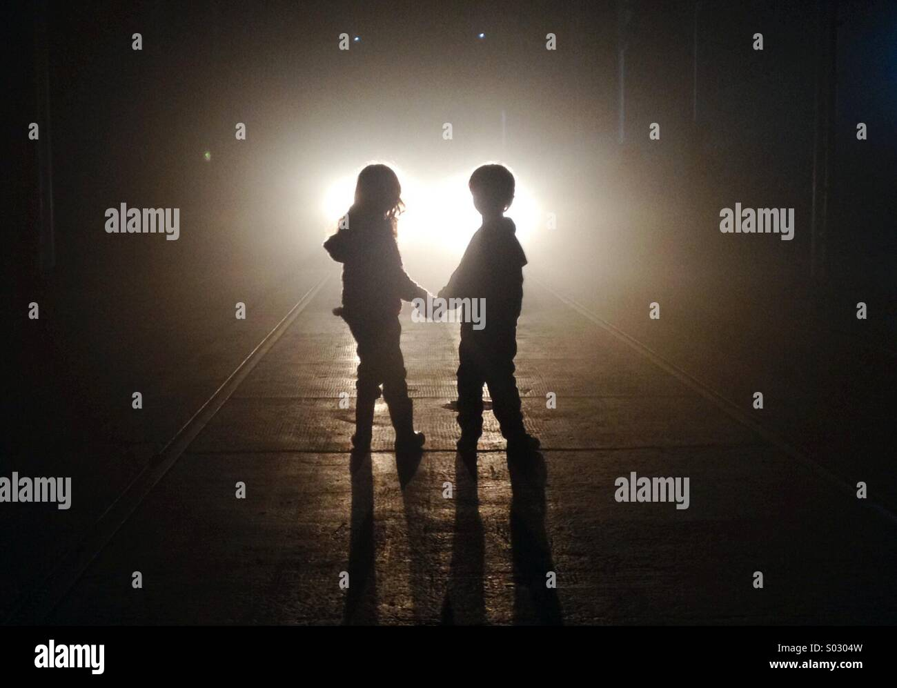 A young boy and girl hold hands, silhouetted against a bright light. - Stock Image