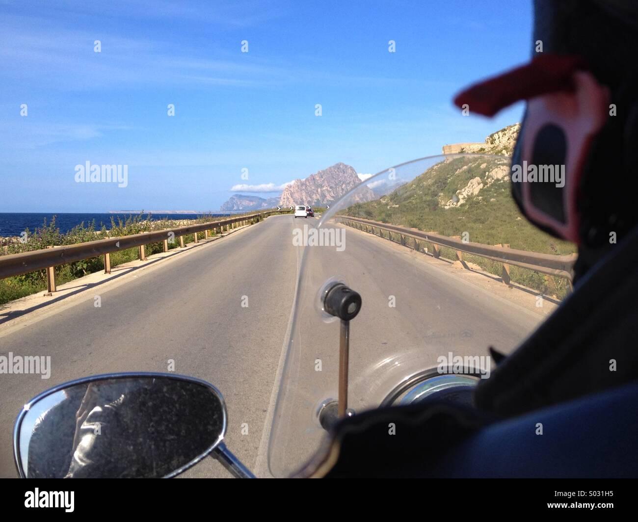 Driving motorbike at sea coast road - Stock Image