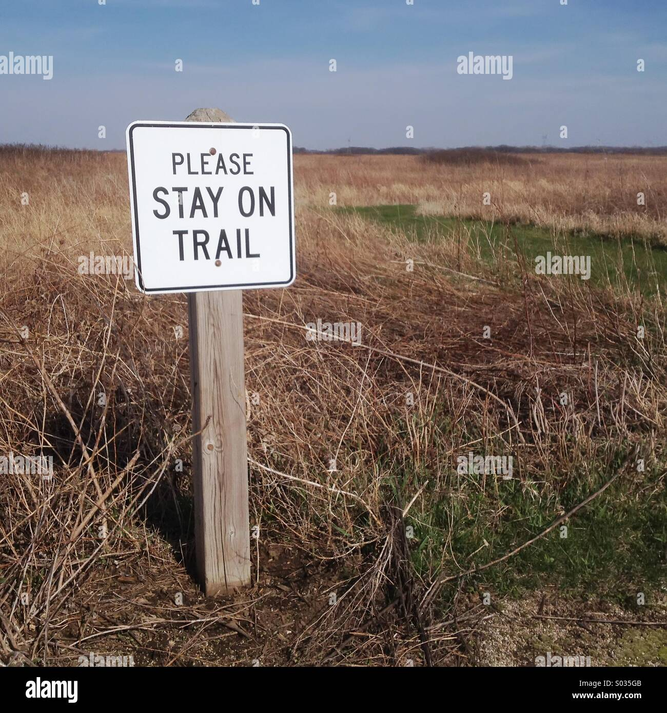 Trail sign on prairie -- for concepts of conformity, normality, cooperation, and routine - Stock Image