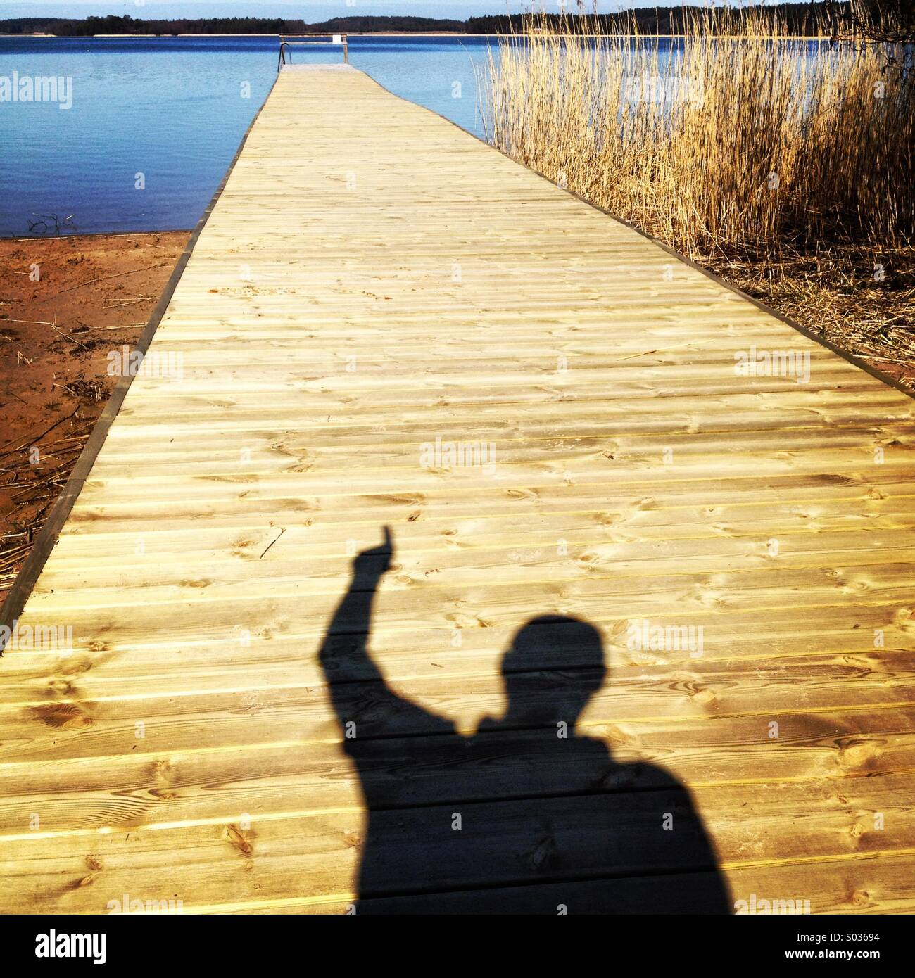 A man in shadow pointing along a long pier on a public beach in Nordic Scandinavia - Stock Image