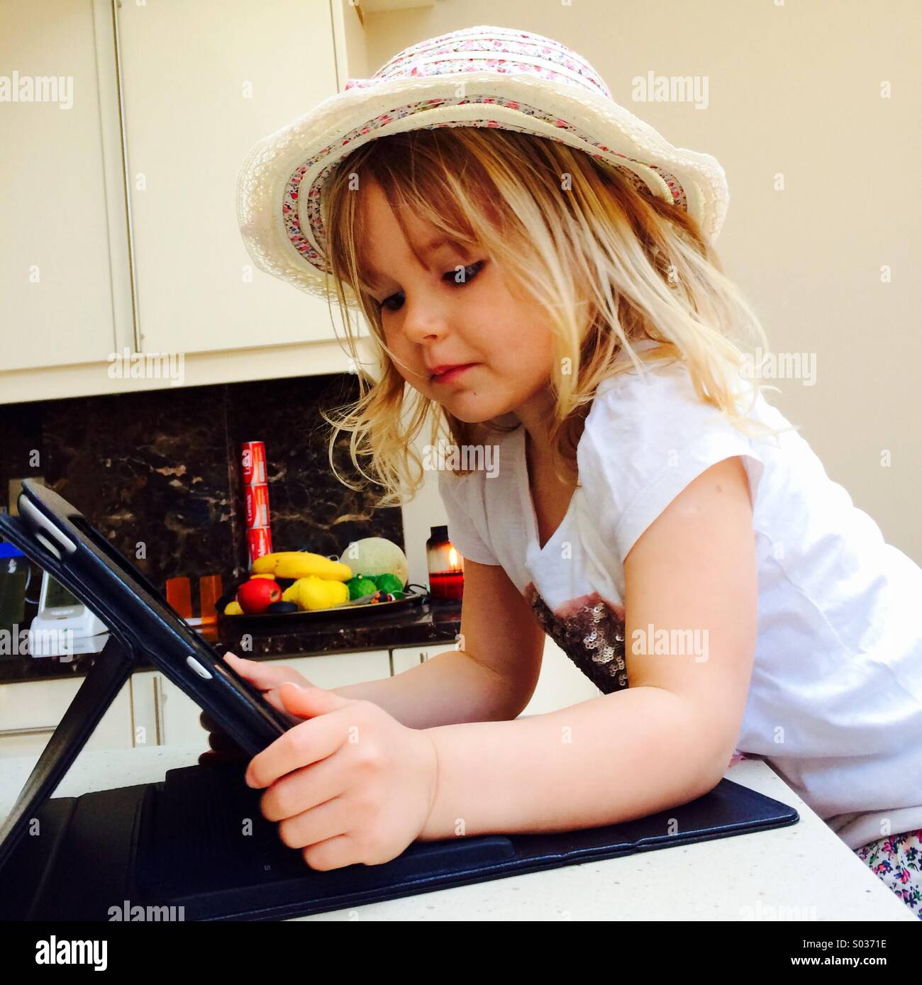 Small girl with a hat on looking at an iPad - Stock Image
