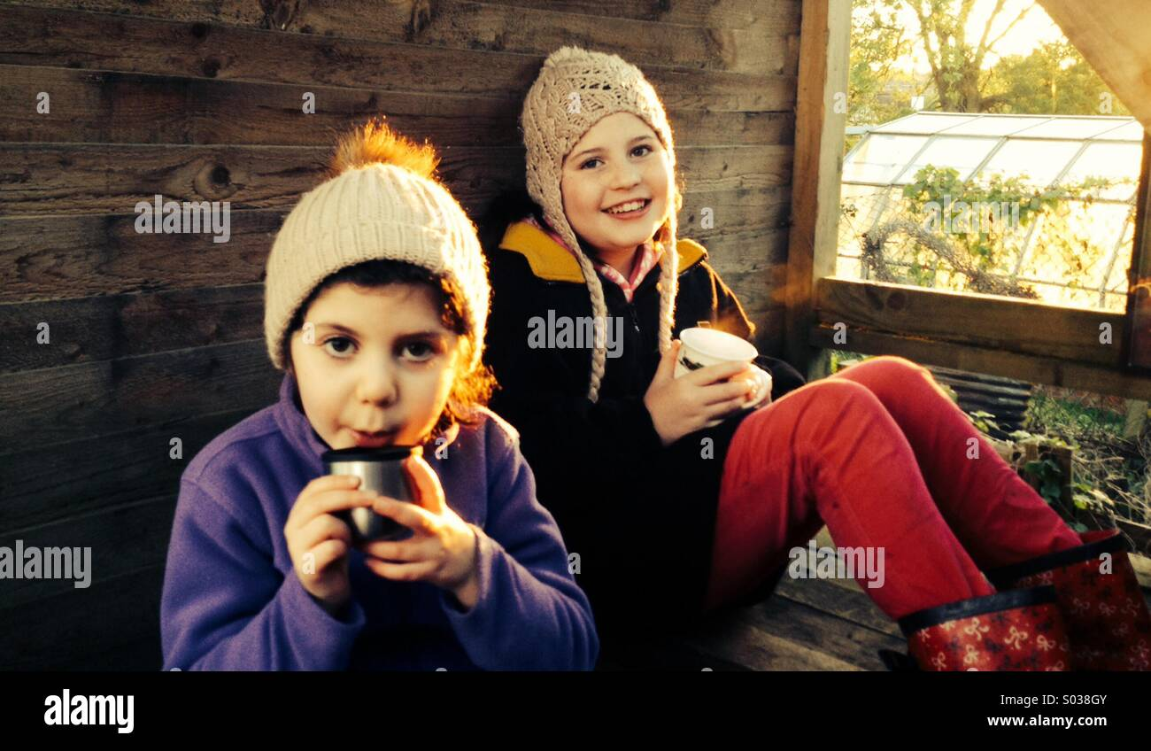 Happy smiling children drinking hot chocolate in a treehouse on a winters day - Stock Image