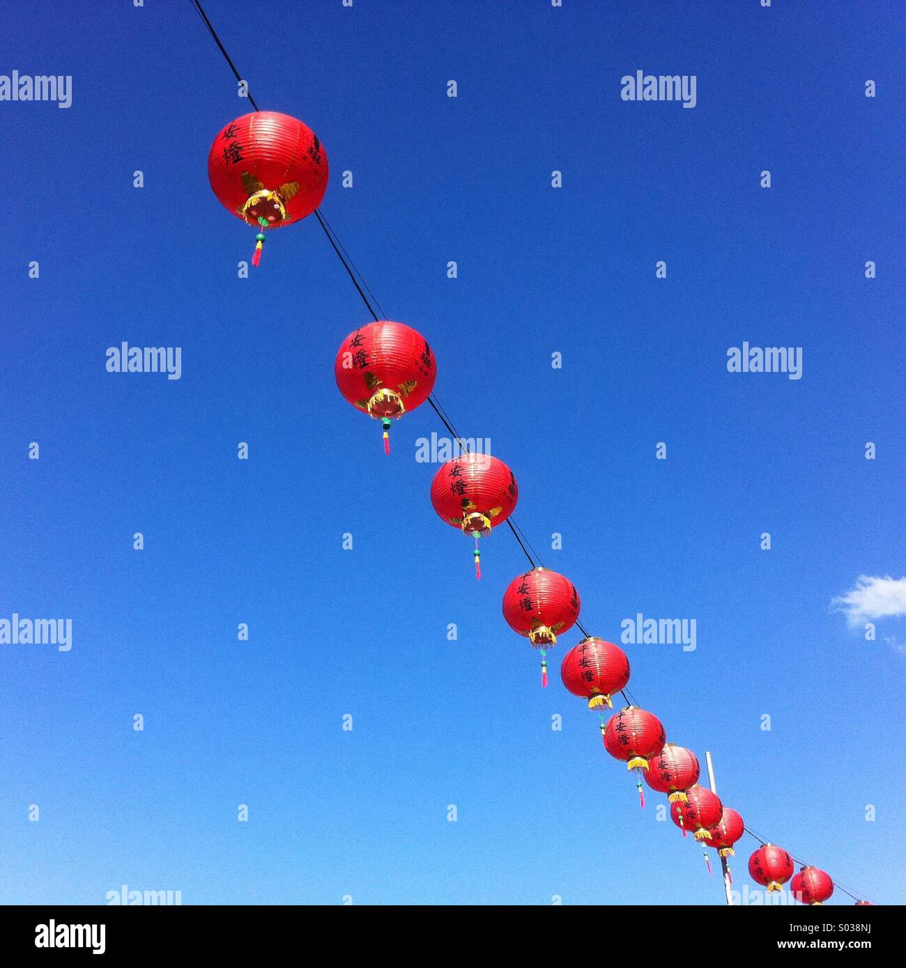 Red lanterns against a blue sky hung for the Buddas birthday festival - Stock Image