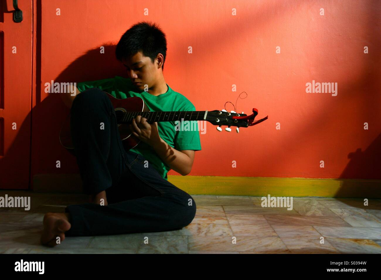 Young asian teen playing guitar in an empty living room - Stock Image