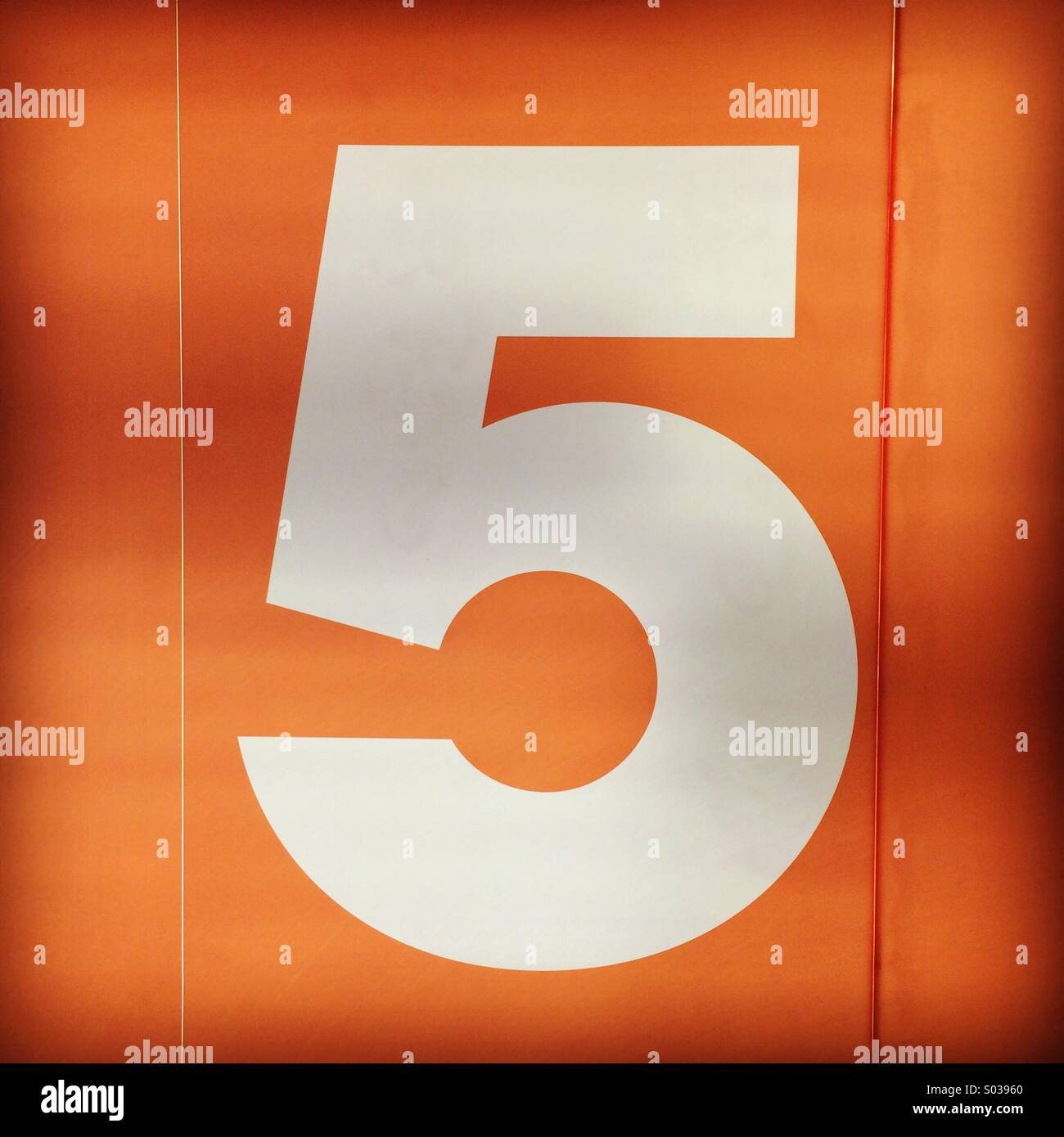 White number five floor number on an orange background. - Stock Image