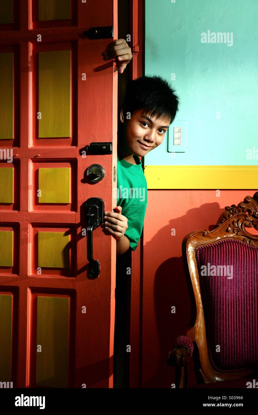 Young asian teen sneaking in into a living room - Stock Image