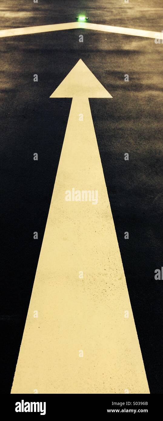 Long white arrow painted on asphalt road pointing at a green cats eye. - Stock Image
