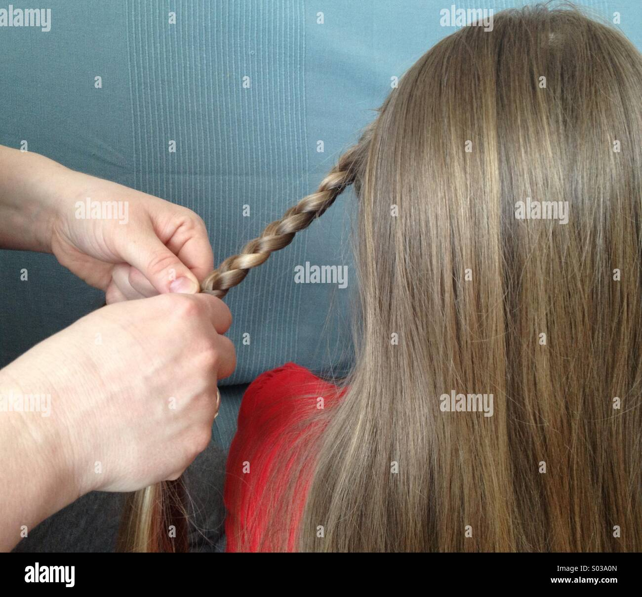 Mother making a braid - Stock Image