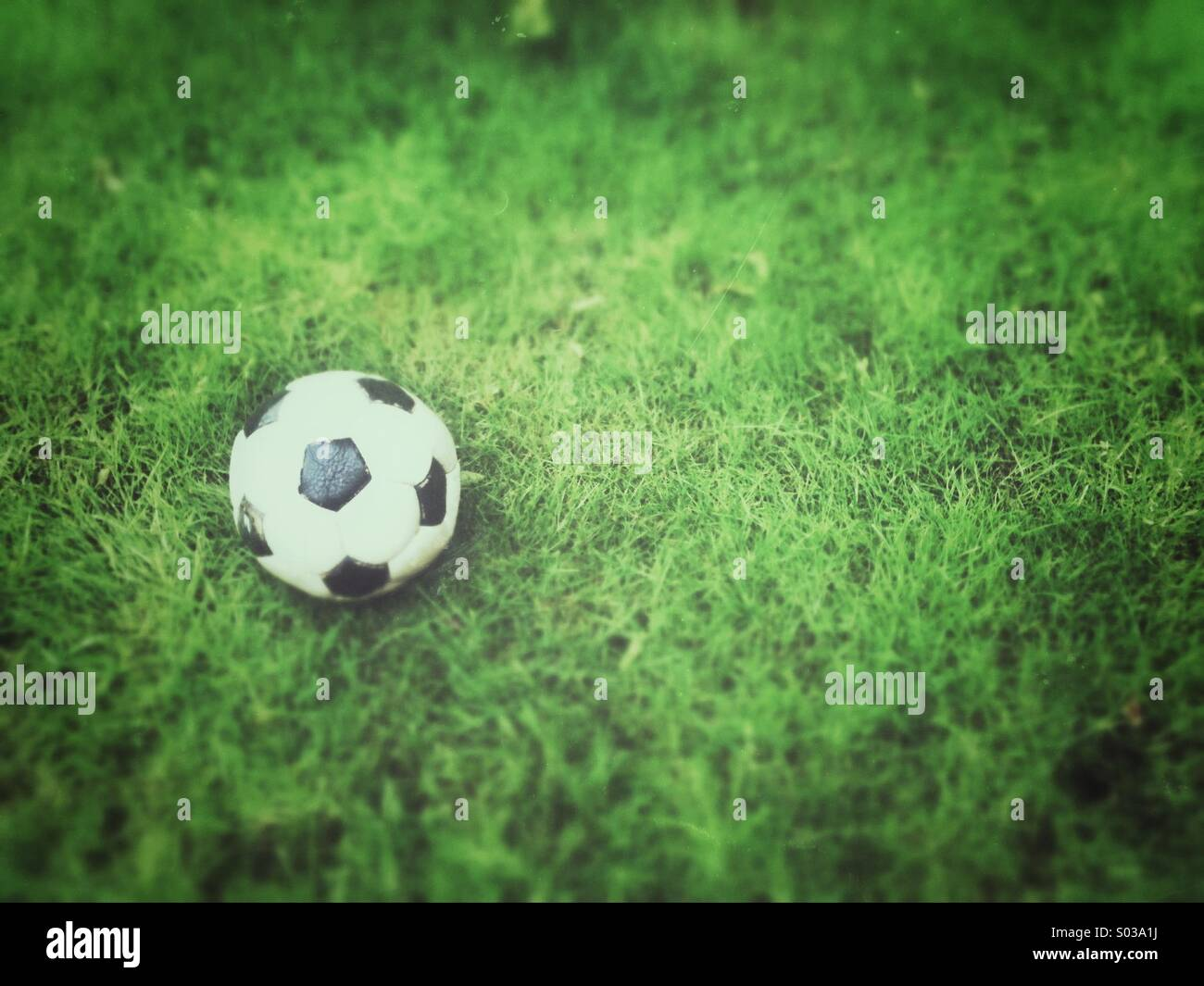 Old football, deflated on grass. Grunge and tilt-shift effects applied. - Stock Image