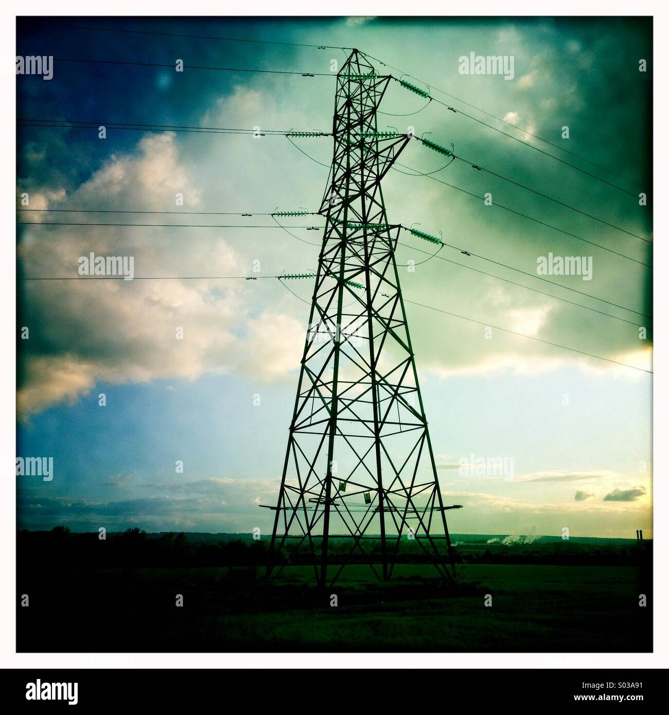 Electricity pylon dark against low sun of an early evening sky - Stock Image
