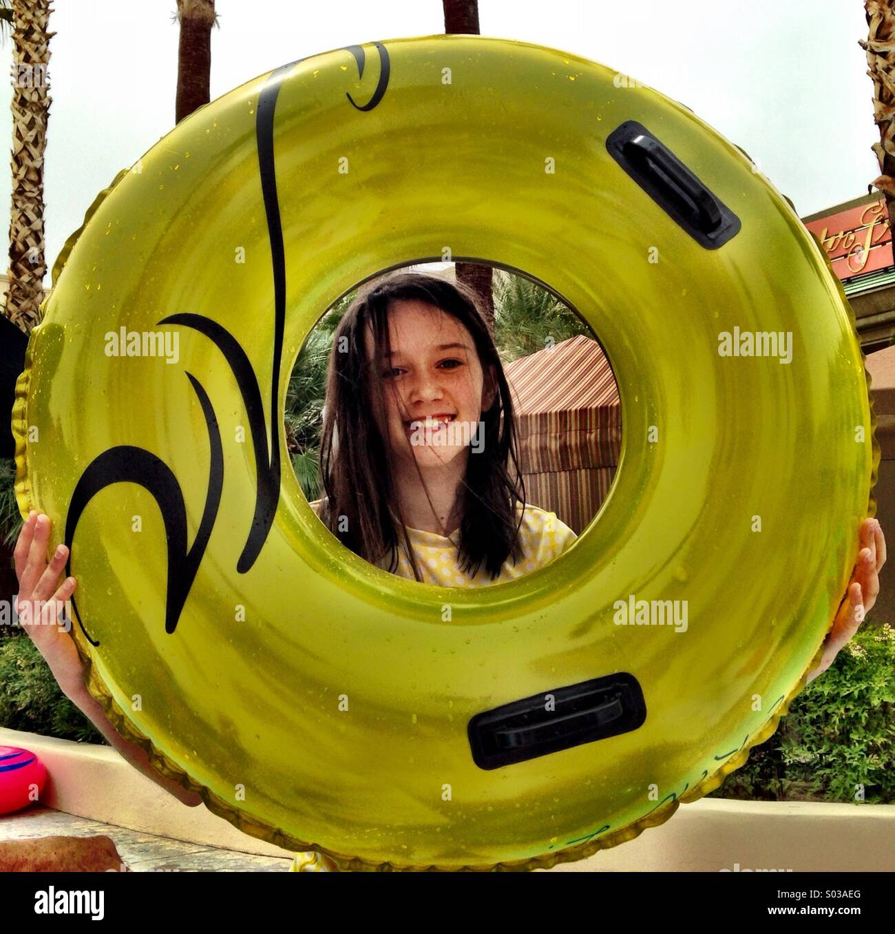 A young girl holds a yellow inner tube. The tube frames her smiling face. - Stock Image