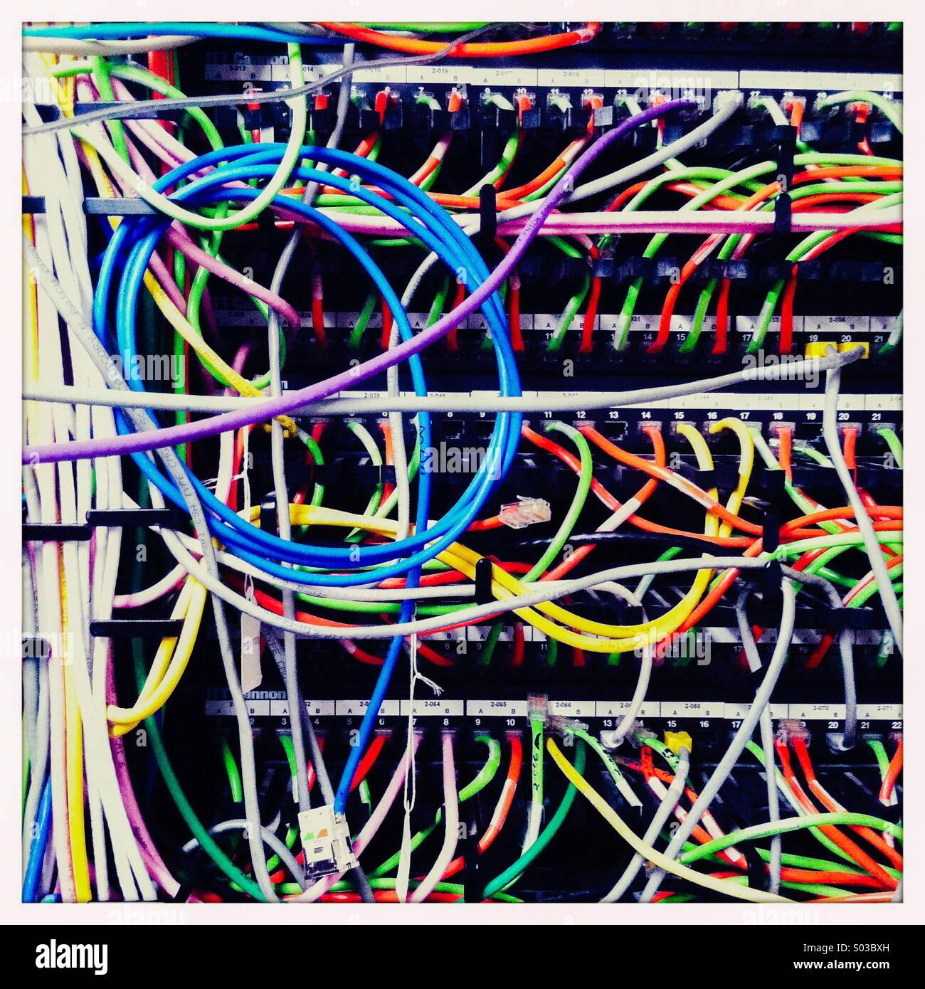 The inside of a telecommunications unit with multiple colored wires. - Stock Image