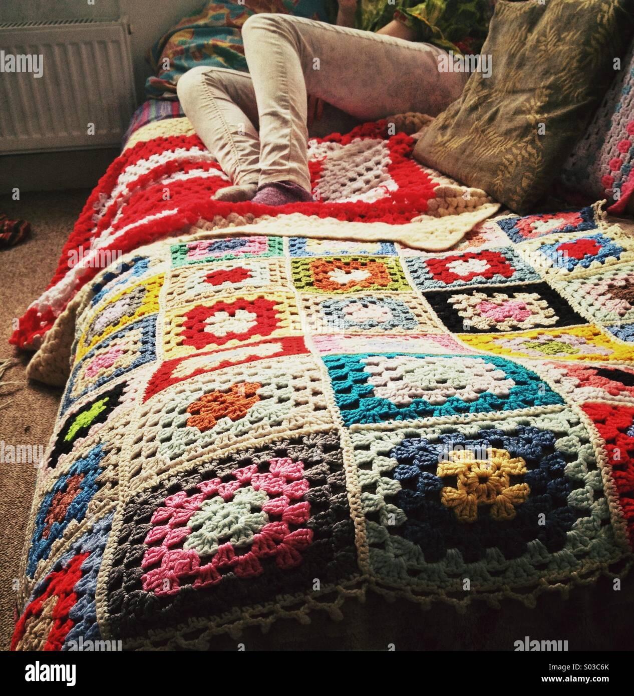 Lazy, teenager sitting on patchwork retro blanket - Stock Image