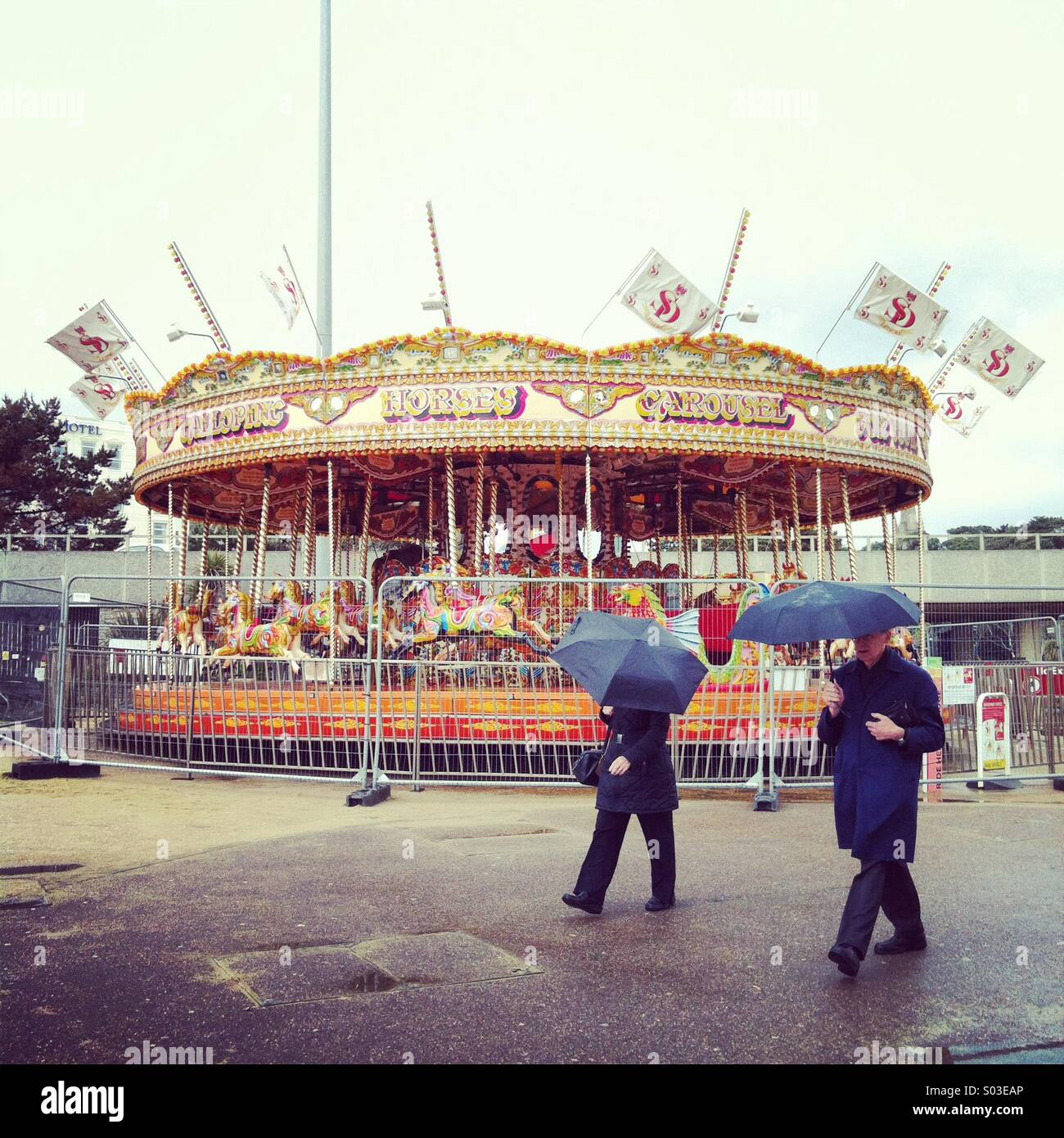 Shut merry go round in Bournemouth on a rainy week day. Two people with black umbrellas passing. - Stock Image