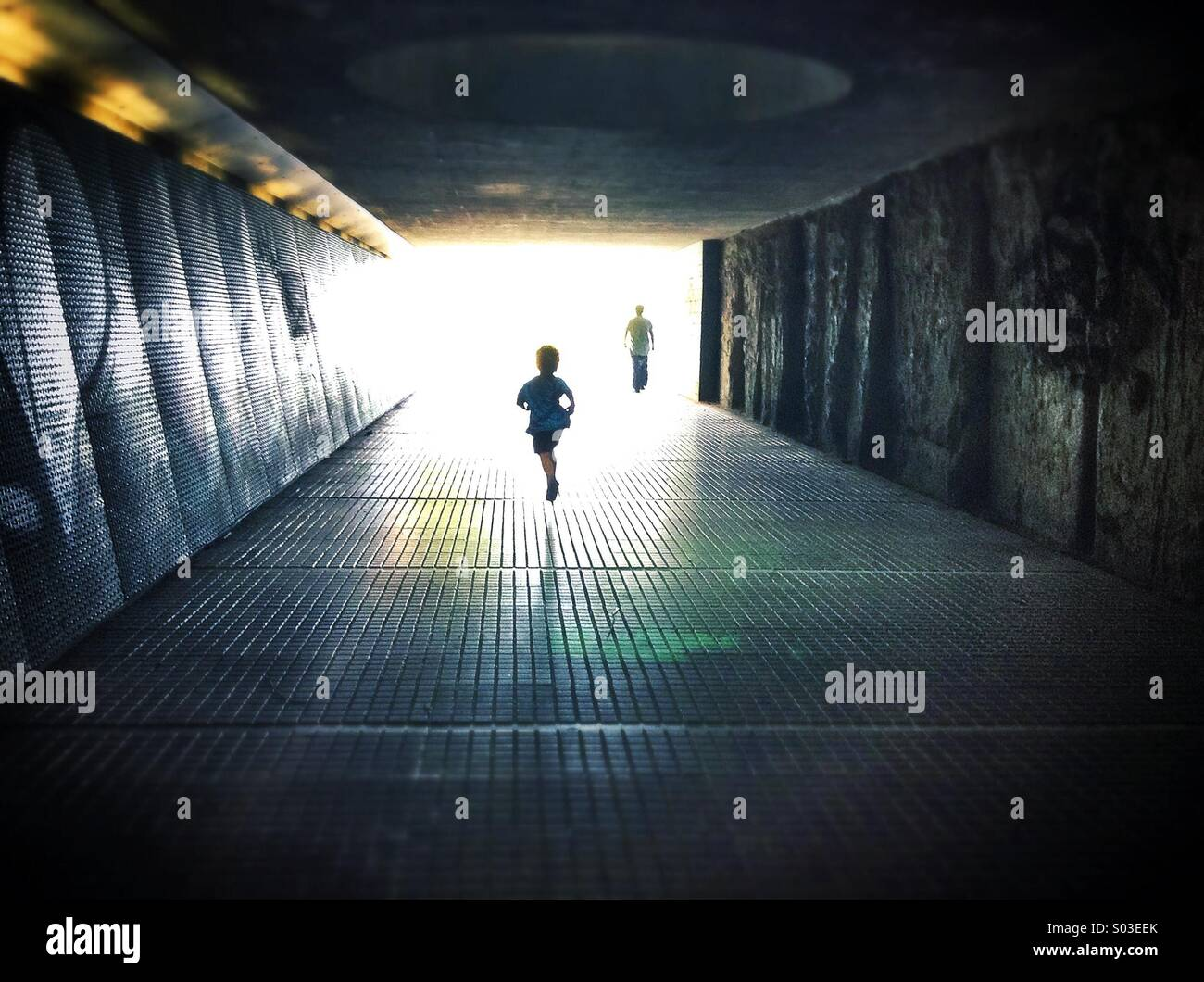 Silhouettes walking through a dark under pass simbolizing light at the end of the tunnel Stock Photo