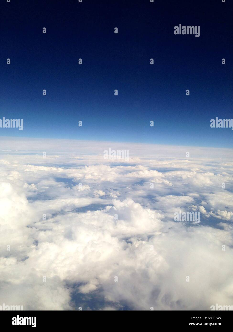 Blue sky above white fluffy clouds - Stock Image