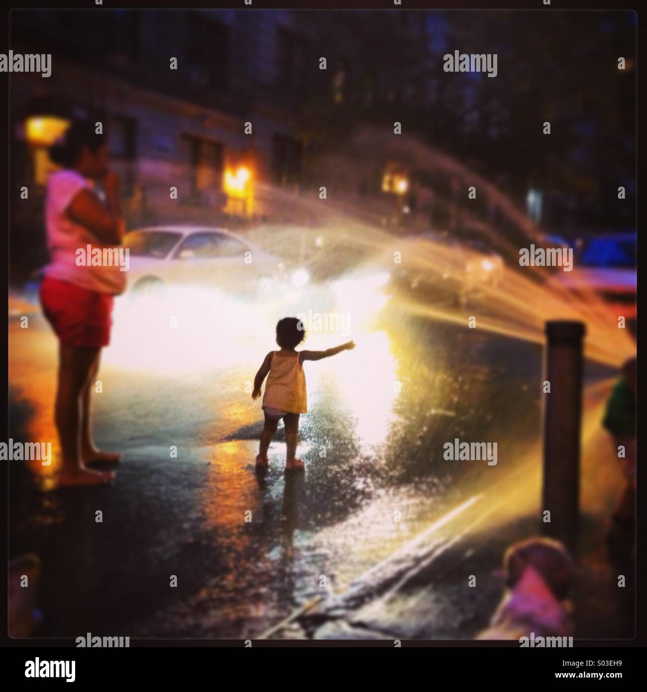 Young child playing in fire hydrant spray - Stock Image