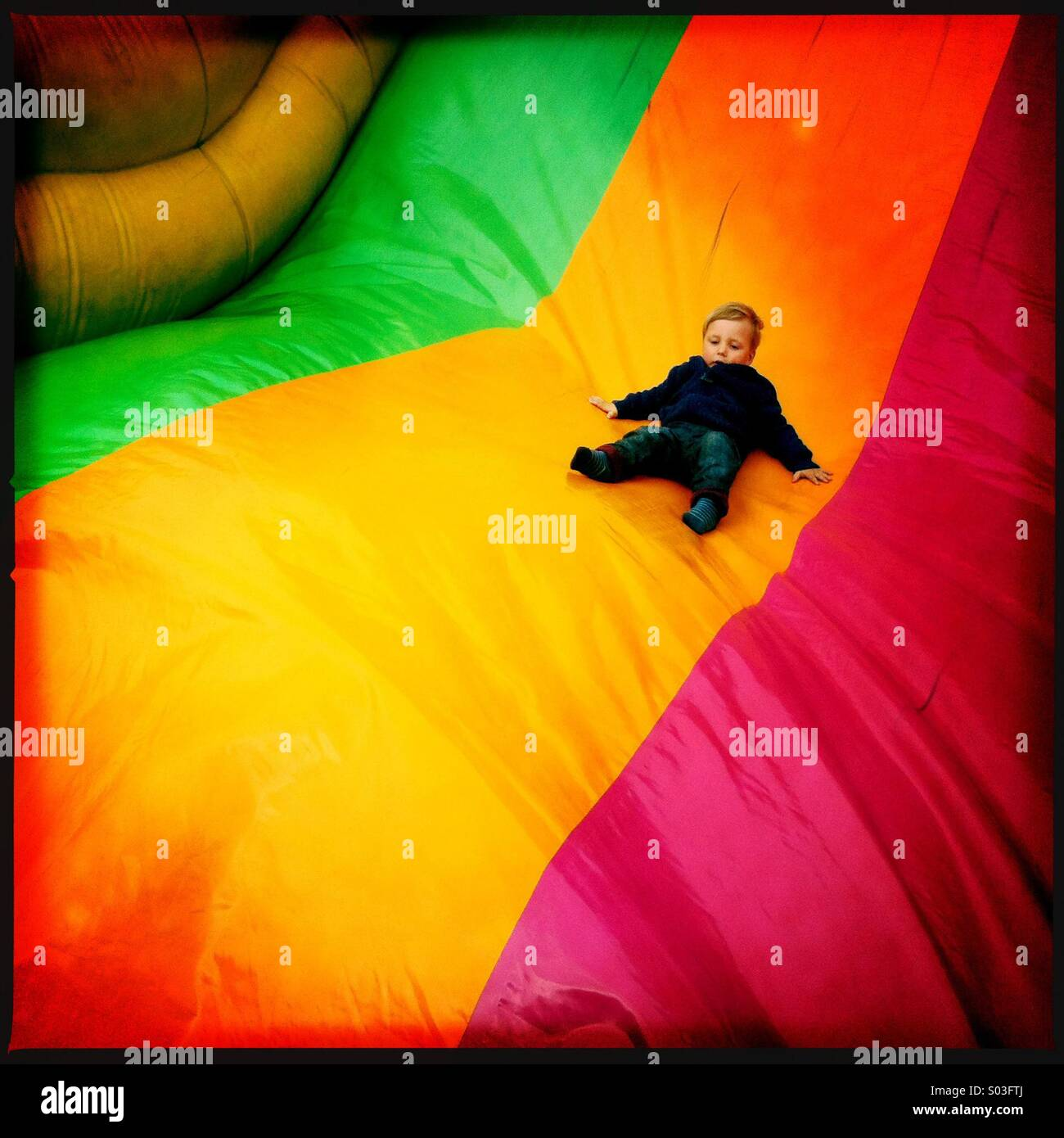 A two year old boy sliding down a large inflatable slide at a fun fair - Stock Image