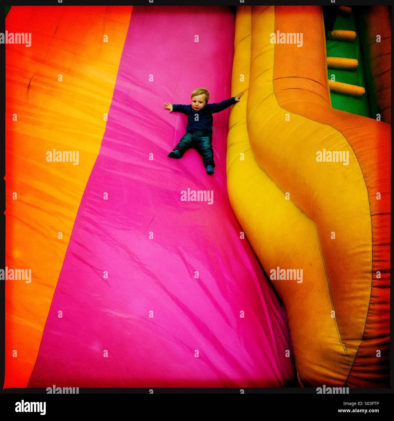 A young two year old boy sliding down aim inflatable slide at a fun fair. The child is showing some degree of fear. - Stock Image