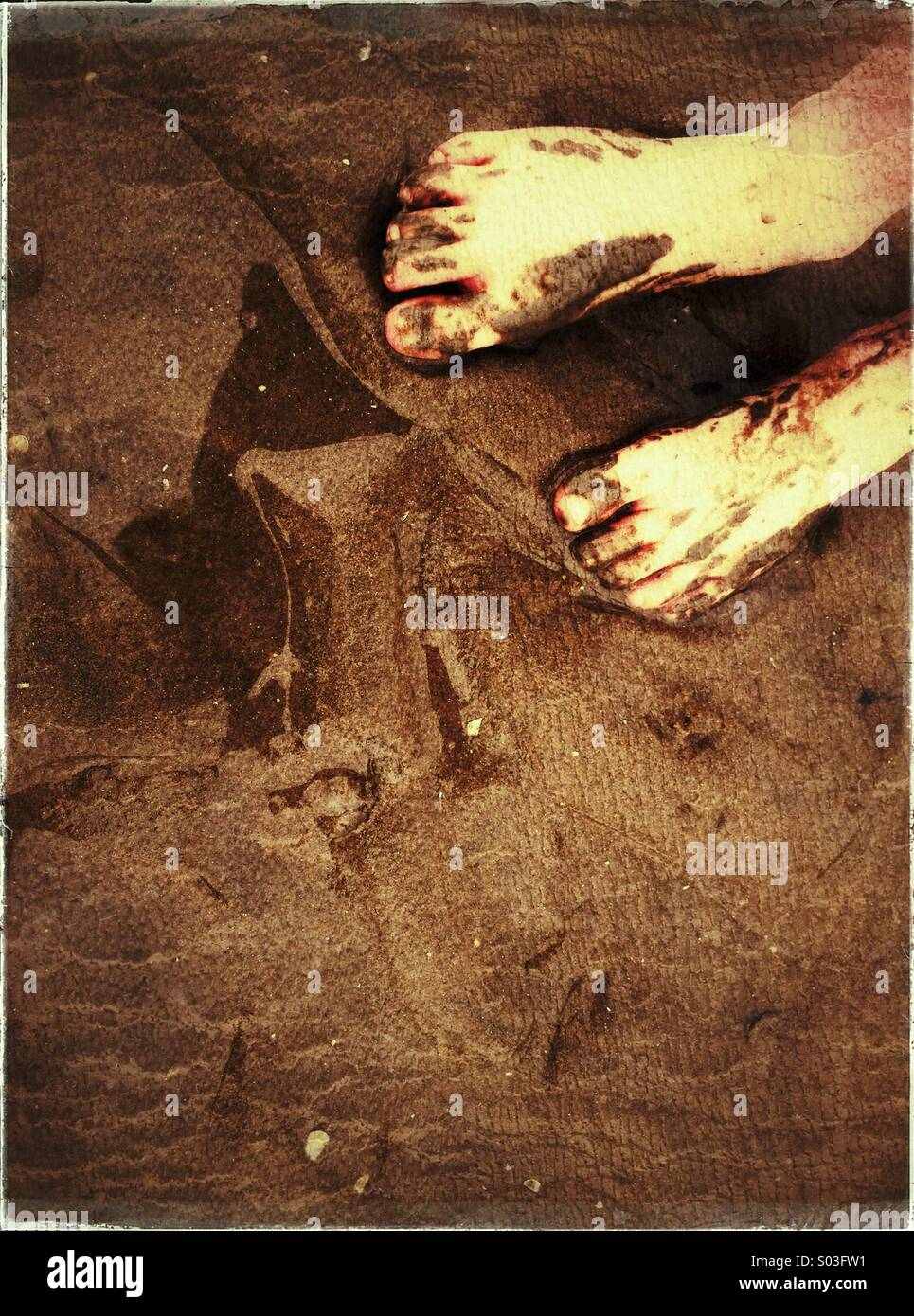 Child's muddy feet in wet sand - Stock Image
