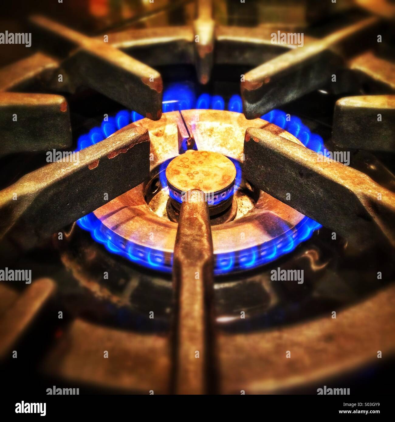 Gas range with blue flame. - Stock Image