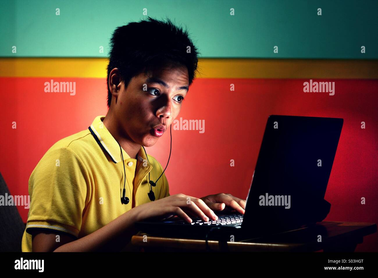 Asian teenager boy working or studying on a laptop computer - Stock Image
