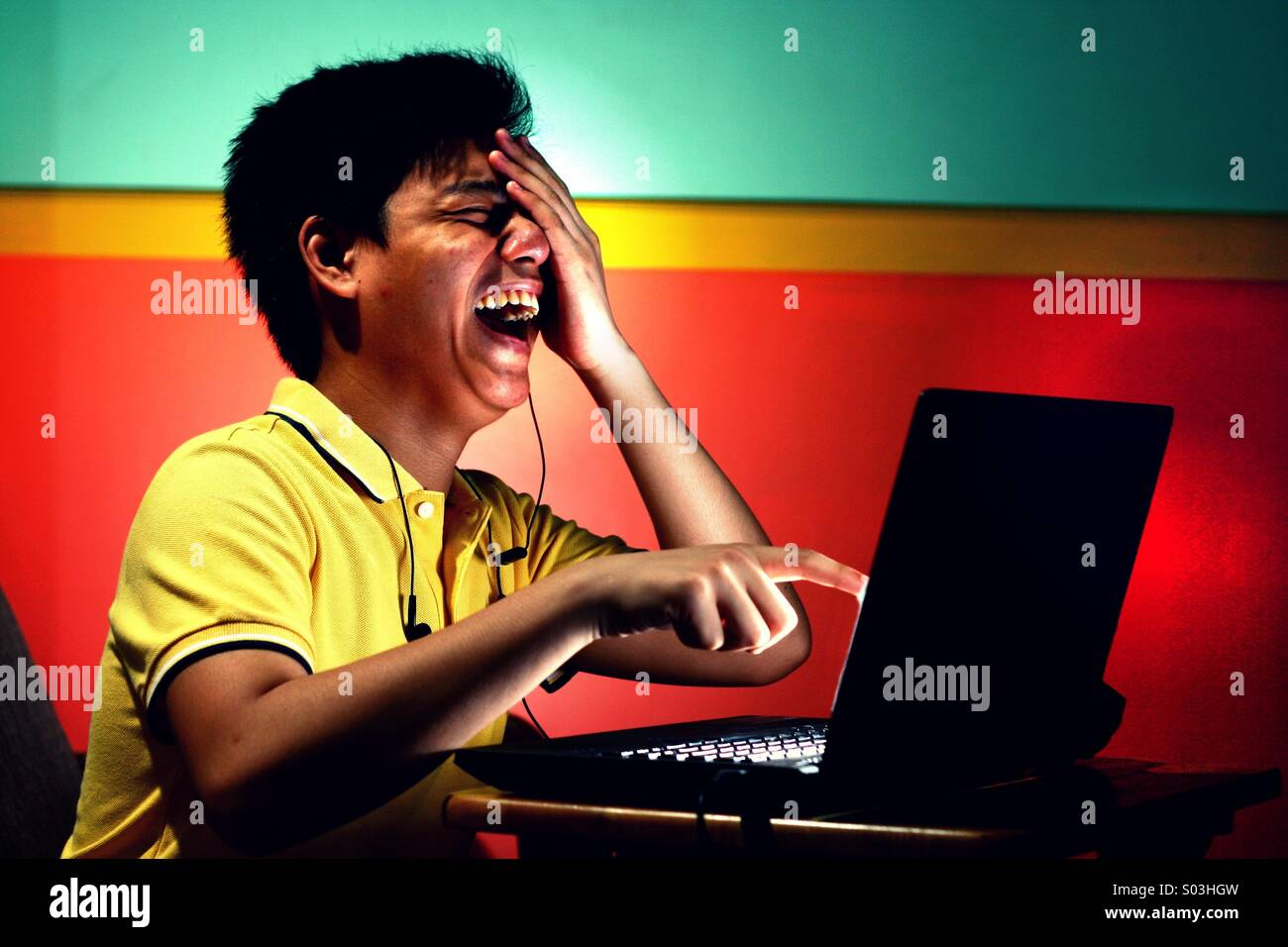 Asian teenager boy working or studying on a laptop computer and laughing hard - Stock Image