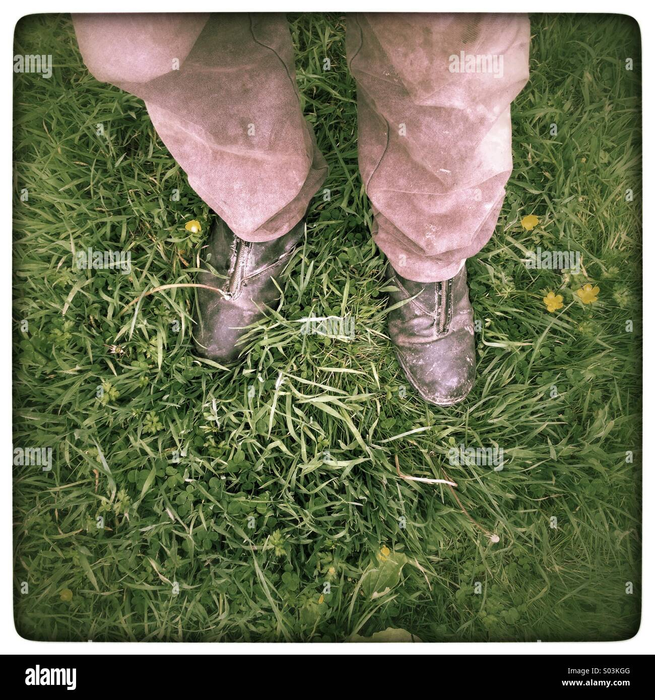 Man's feet in grass wearing boots - Stock Image