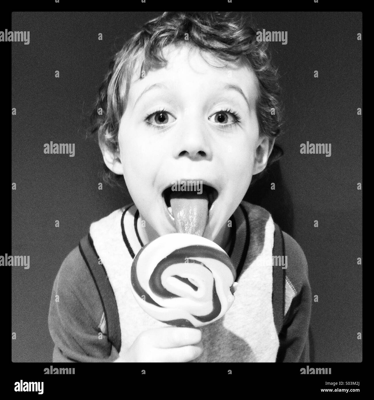 Boy licking a Lollypop - Stock Image